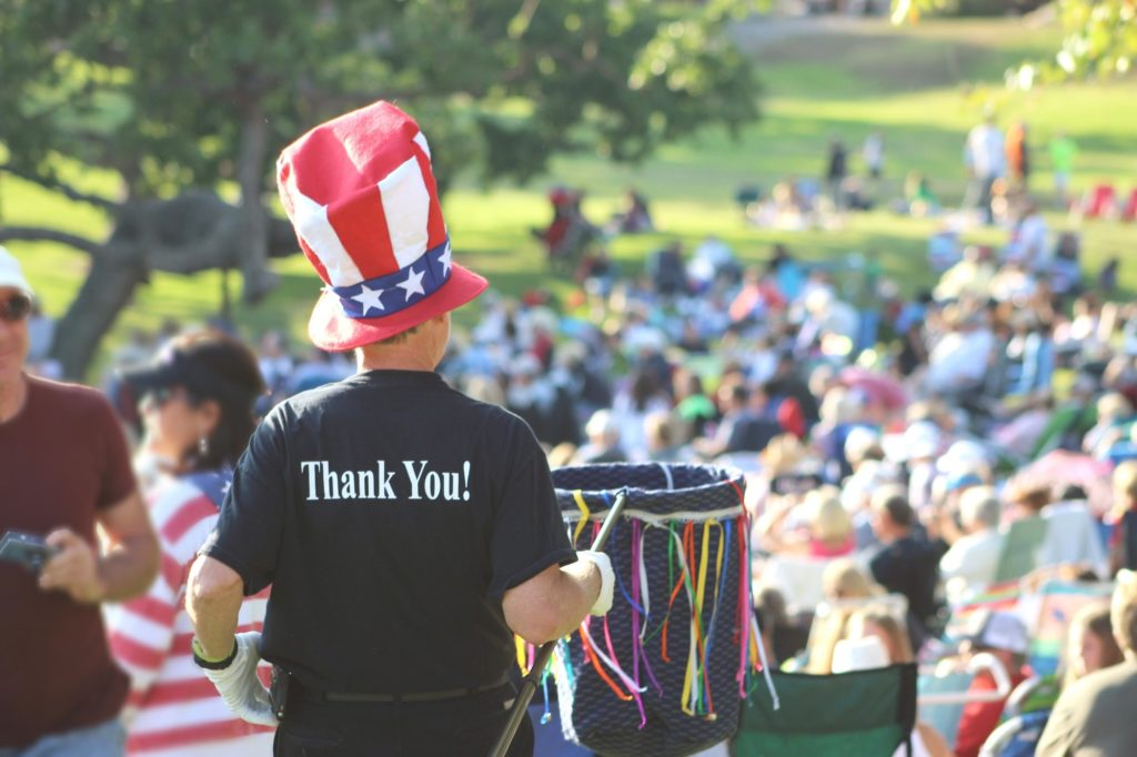 A man is collecting donations at a concert in the park. He is wearing a shirt that says Thank You.