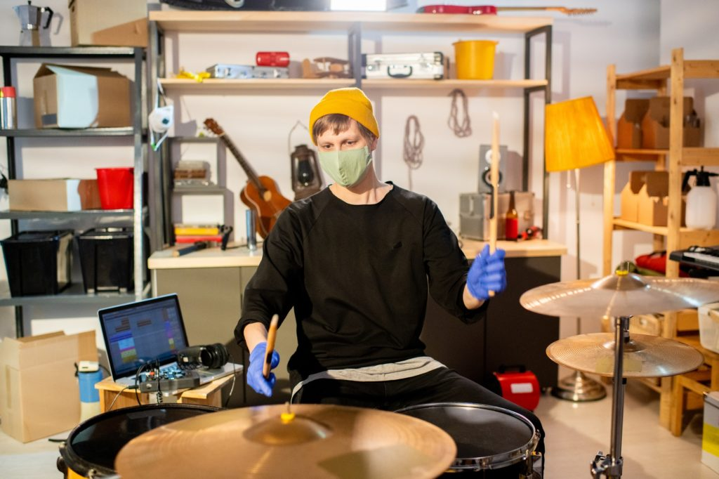 Contemporary young man in protective gloves and mask making new music
